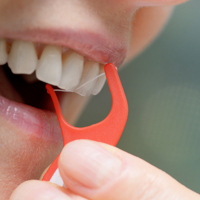 """Woman cleaning her teeth with orthodontic flosser"" stock image"