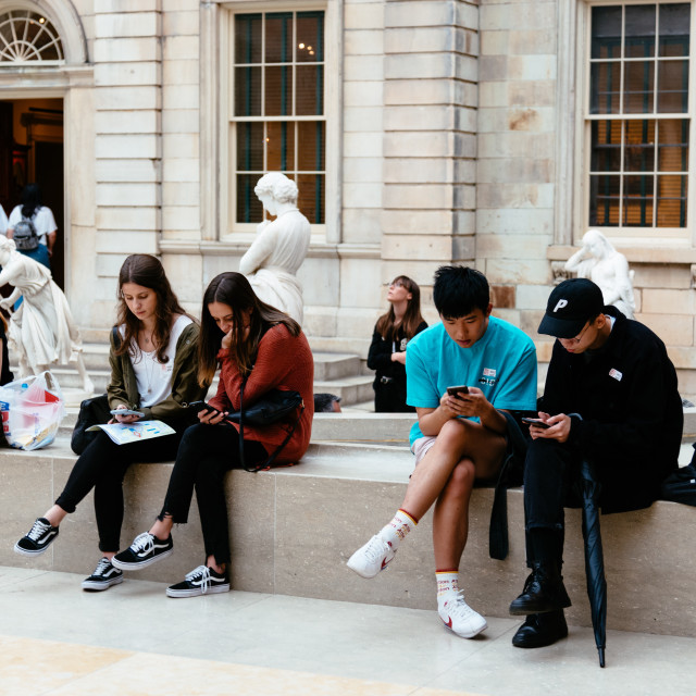 """Young people sitting on museum with mobile phones"" stock image"