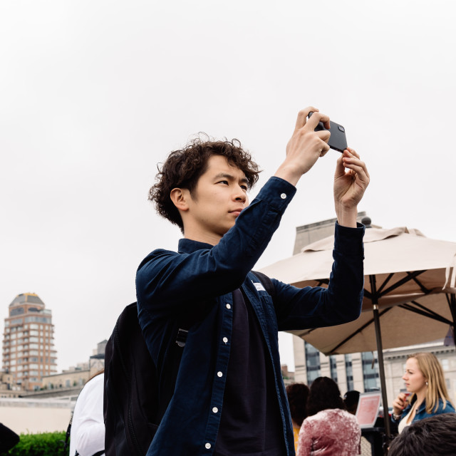 """Young man taking photos of the skyline of New York"" stock image"