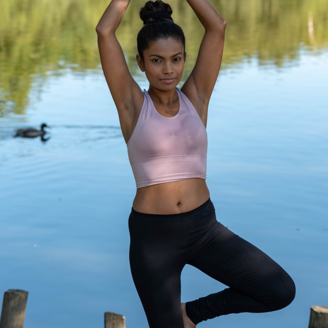 """Young woman performs yoga by lake"" stock image"