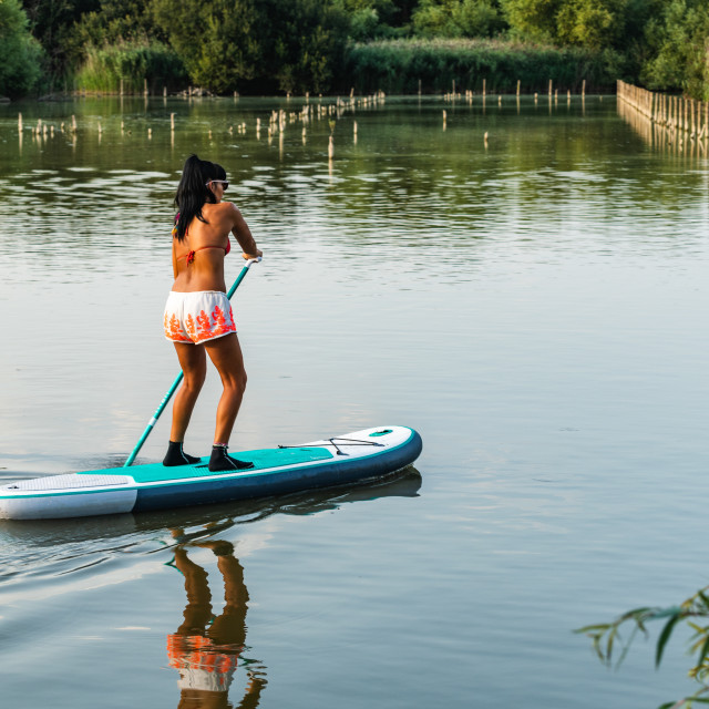 """Woman stand up paddleboarding"" stock image"