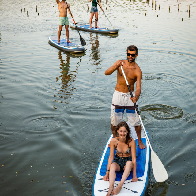 """Man and women stand up paddleboarding"" stock image"