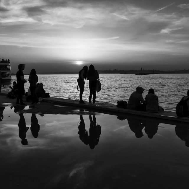 """Silhouettes of some young people with beautiful reflections on the water at sunset"" stock image"