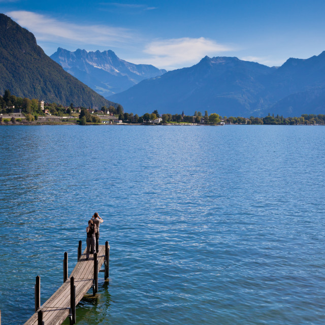 """""""Taking photos on the pier by Chillon Castle in Montreux overlooking Lake Geneva and nearby mountains"""" stock image"""