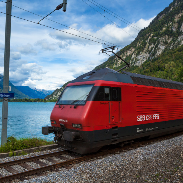 """""""Swiss train on track by Lake Thun after departing from Interlake"""" stock image"""