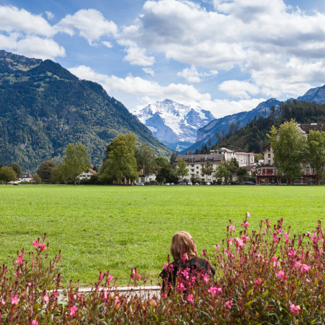 """""""Woman sitting on park bench in central Interlaken with the snow"""" stock image"""