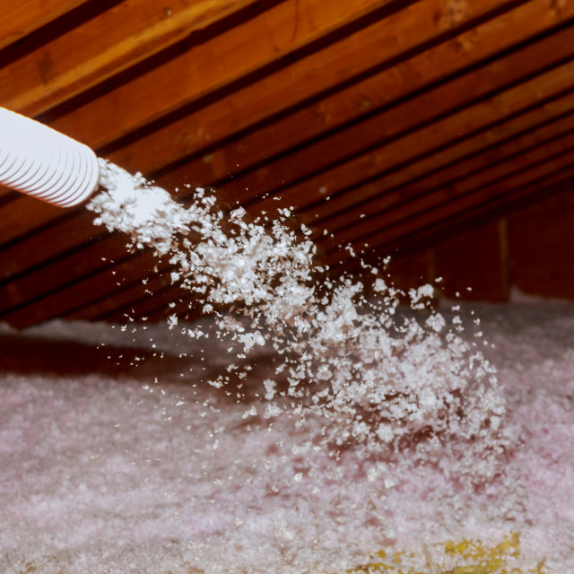 """Spraying Blown Fiberglass Insulation for roof - technician spraying foam..."" stock image"