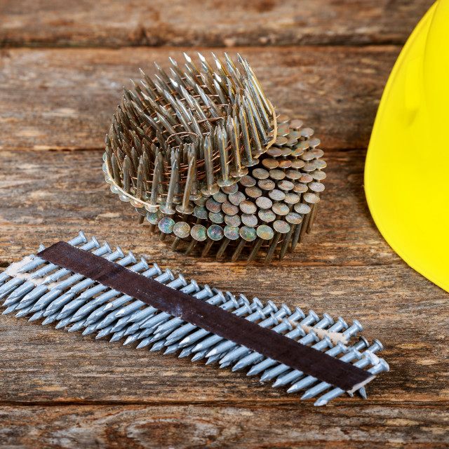 """""""Tape of nails pneumatic hammer anc helmet for construction a wooden background."""" stock image"""