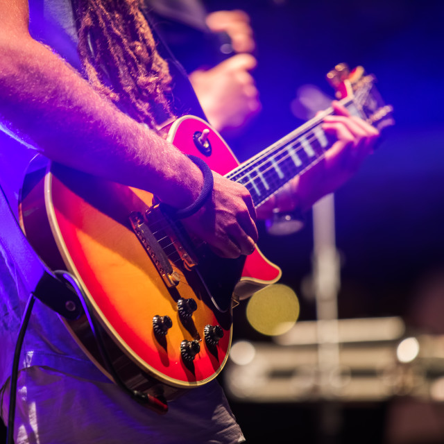 """Guitarist playing on electric bass guitar on stage. Colorful, so"" stock image"