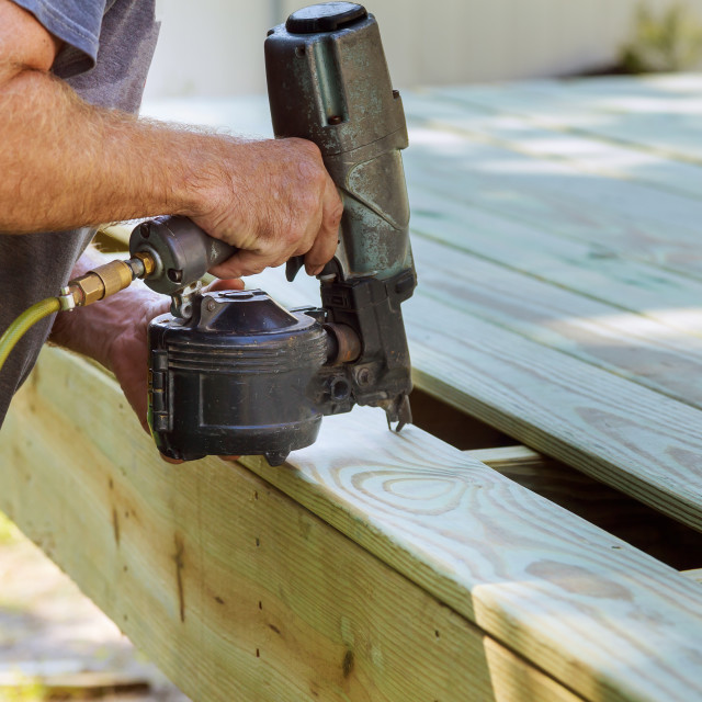 """Installing Wood on deck, patio construction man using pneumatic gun"" stock image"
