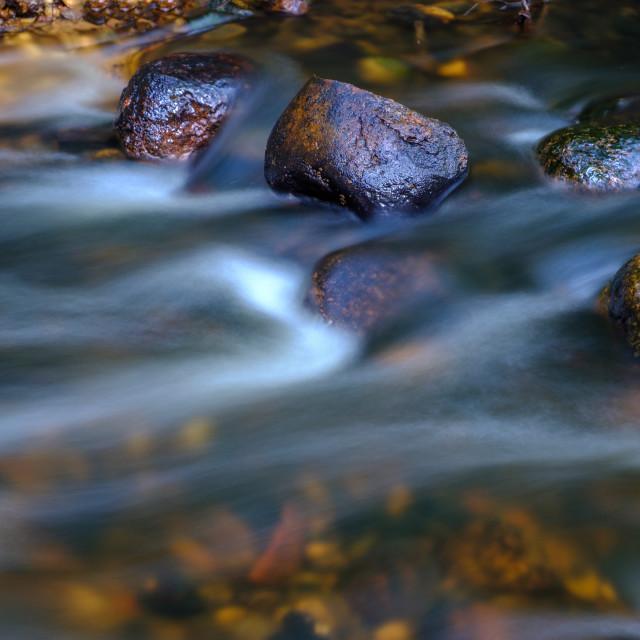 """Water stream flowing between rocks"" stock image"