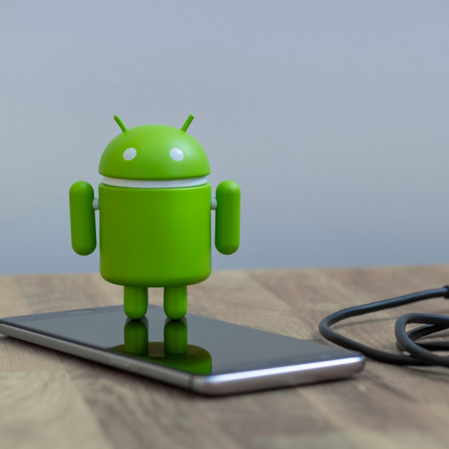 """Google Android figure standing on a smart phone"" stock image"