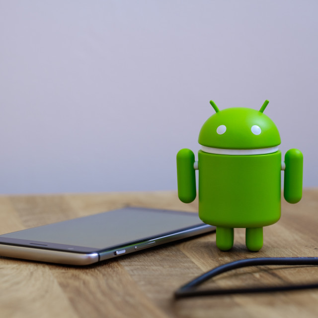 """Google Android figure standing next to smart phone"" stock image"