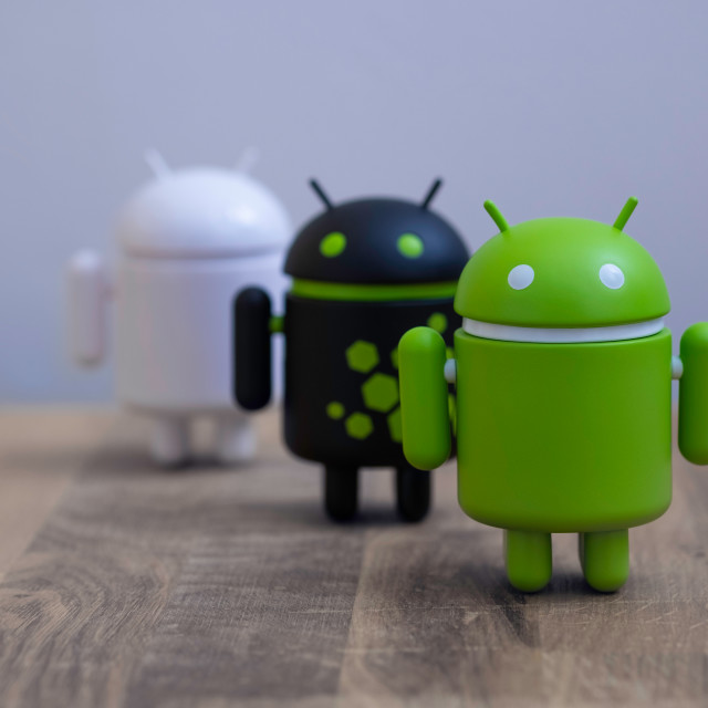 """Google Android figures standing on desk"" stock image"