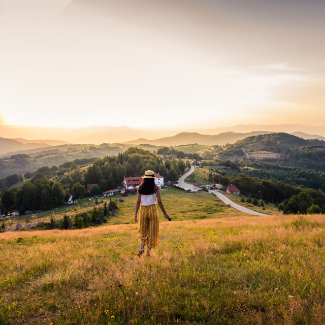 """Woman walking down the hill at sunset"" stock image"