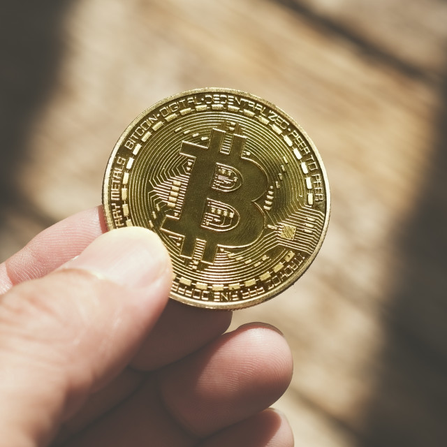"""Hand Holding Bitcoin Against Brown Wood Background"" stock image"