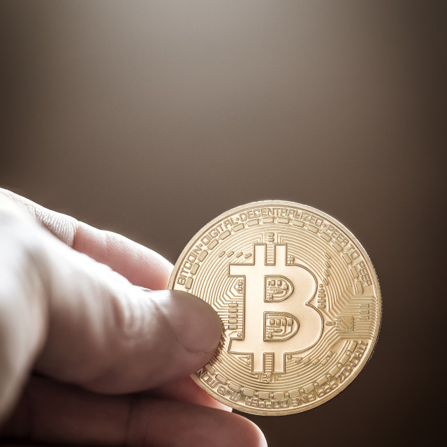 """Hand Holding Bitcoin Against Brown Background"" stock image"