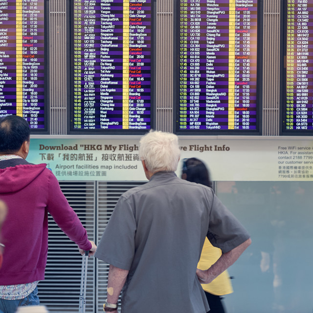 """Airport Flight Gate Display and waiting passengers"" stock image"