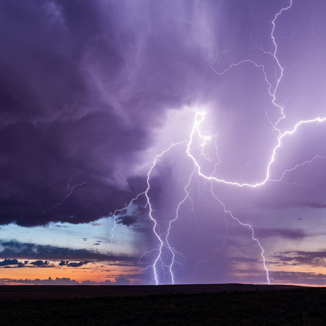 """Lightning bolts strike from a thunderstorm at sunset."" stock image"