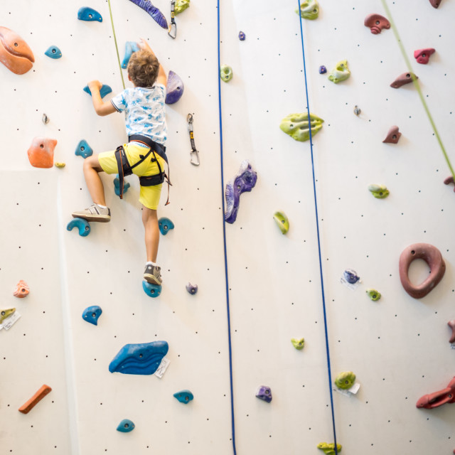 """young boy is climbing on artificial climbing wall"" stock image"