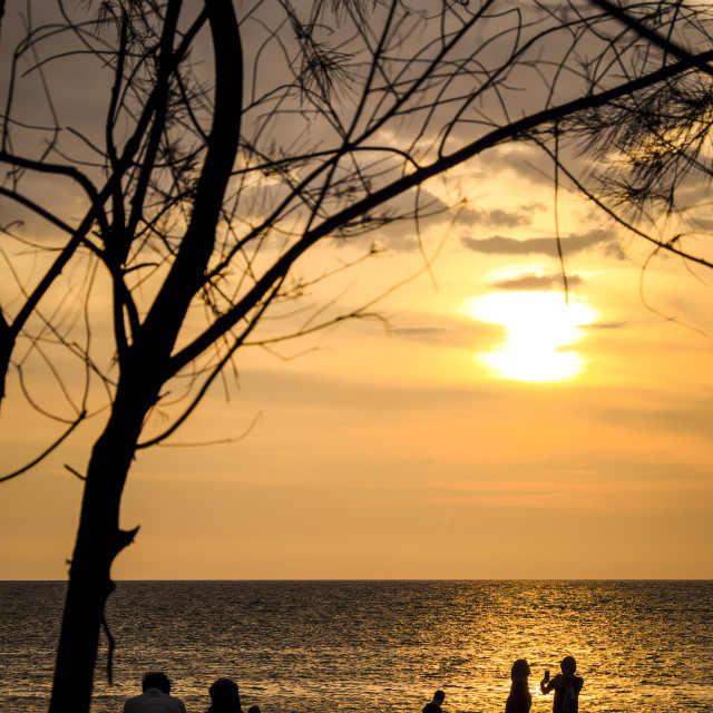 """Silhouette of people at sunset beach"" stock image"