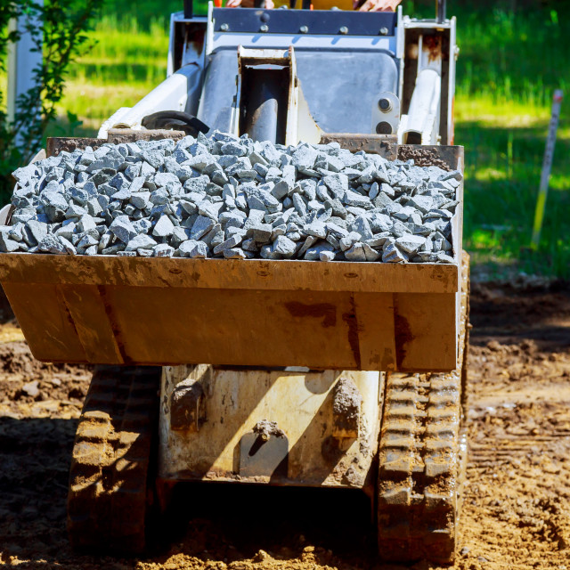 """""""Loader moving with uploaded bucket with stone gravel during construction works."""" stock image"""