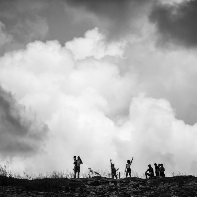 """a group of people stand on a ridge with dramatic clouds behind them"" stock image"