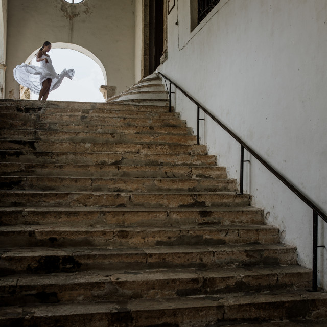 """A lady dancing in a white dress at the top of the stairs in a colonial building"" stock image"