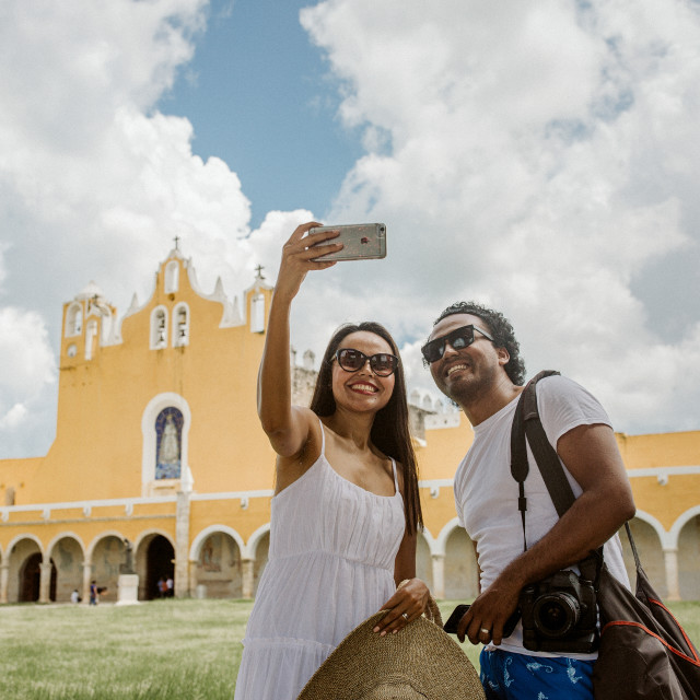 """two people take a selfie in front of a mexican monastery in yucatan"" stock image"