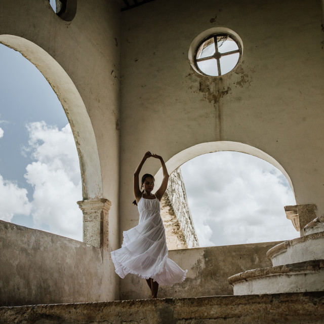 """a lady dances in a white dress in a monastery in between two large windows in mexico"" stock image"