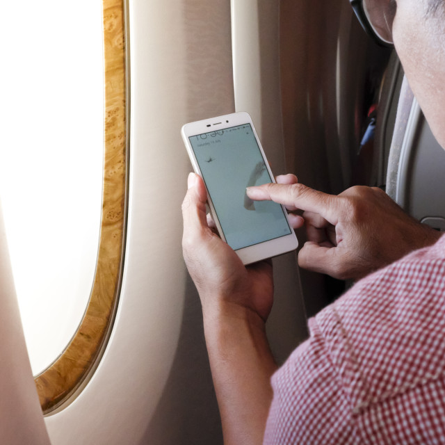 """Passenger Using Mobile Device in Airplane"" stock image"