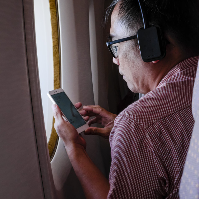 """Adult Male Passenger Using Mobile Device In Flight"" stock image"