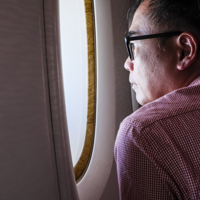 """Adult Male Looking Out of Airplane window"" stock image"