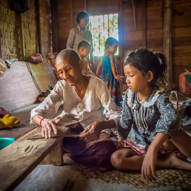 """Old woman making incense as child watches, village home near Siem Reap,..."" stock image"