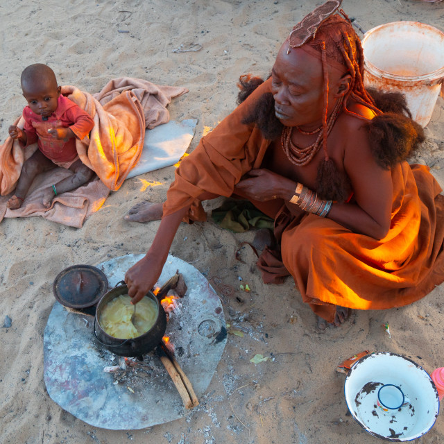 """""""One senior red ochred, Himba woman with her child cooking on an open fire,..."""" stock image"""