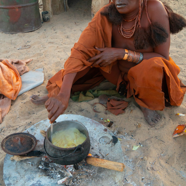 """""""One senior red ochred, Himba woman cooking her meal on an open fire, Puros..."""" stock image"""