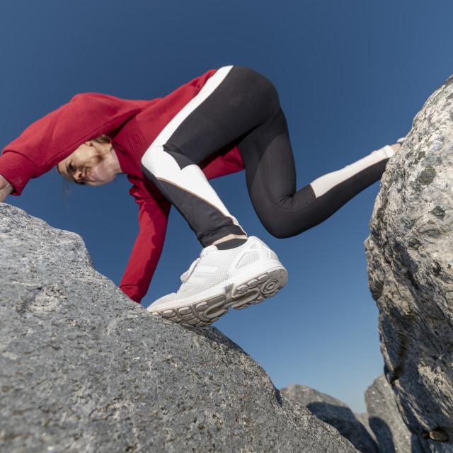 """woman clambering across rocks, bouldering."" stock image"