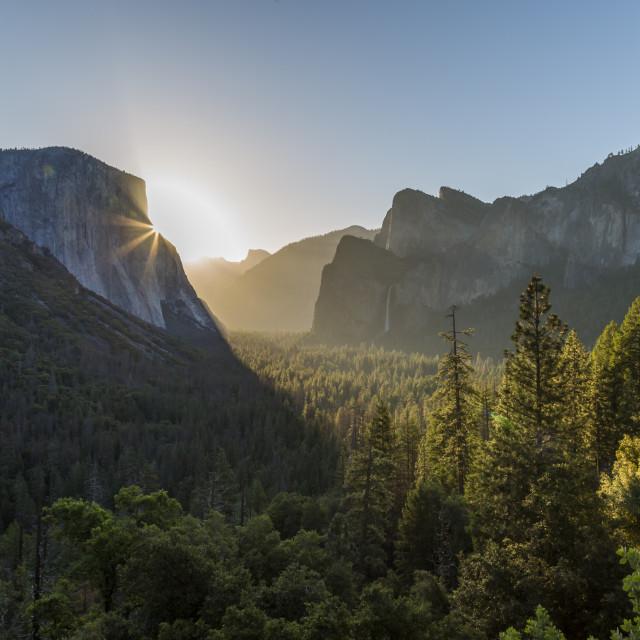 """Morning view of sun peaking round El Capitan, Yosemite National Park, UNESCO..."" stock image"