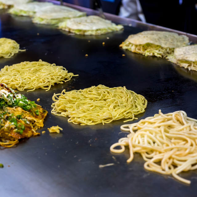 """Okonomiyaki being prepared on a large griddle."" stock image"