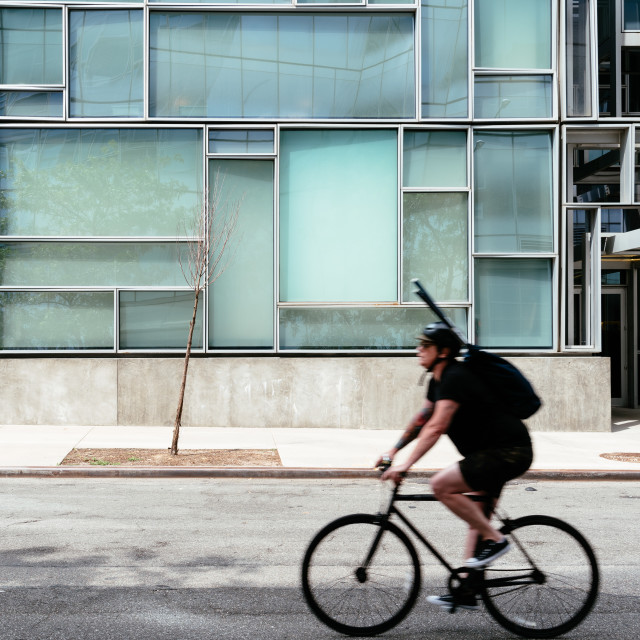 """Cyclist riding against minimalist style building NYC"" stock image"
