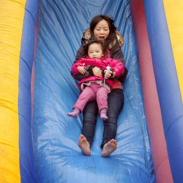 """An Asian American mom holds her daughter as they go down an inflated amusement park slide at a winter carnival in Mission Viejo, CA."" stock image"