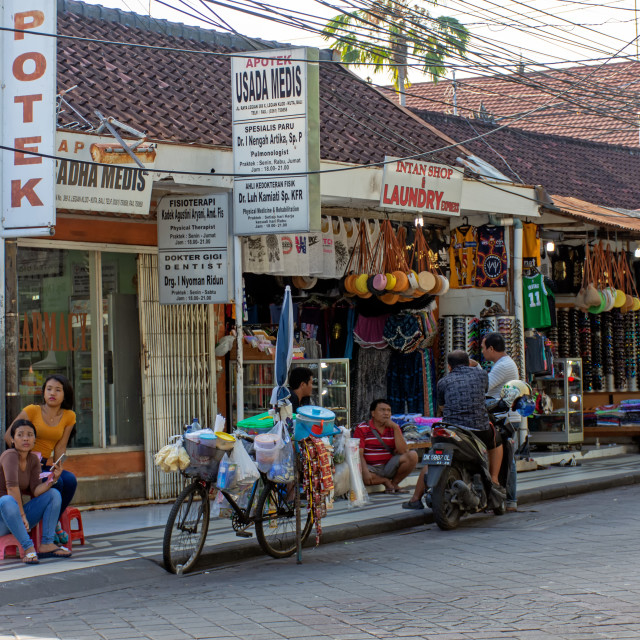 """Kuta, Indonesia - September 14, 2018: Vendor waiting for customer at Legian street. Legian is famous among tourist for nightclub and entertainment."" stock image"
