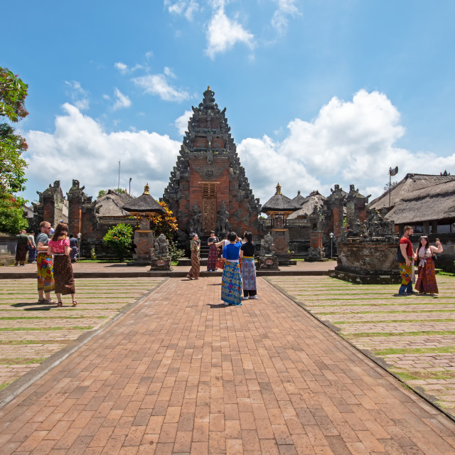 """""""Bali, Indonesia - September 15, 2018: Tourists at Puseh temple, located at Batuan village. It is a Balinese temple with interesting stone carvings & sculptures, sarongs required for entrance."""" stock image"""