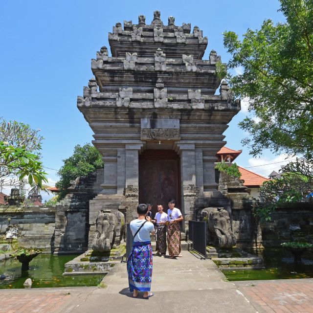 """Bali, Indonesia - September 15, 2018: Tourists at Puseh temple, located at Batuan village. It is a Balinese temple with interesting stone carvings & sculptures, sarongs required for entrance."" stock image"