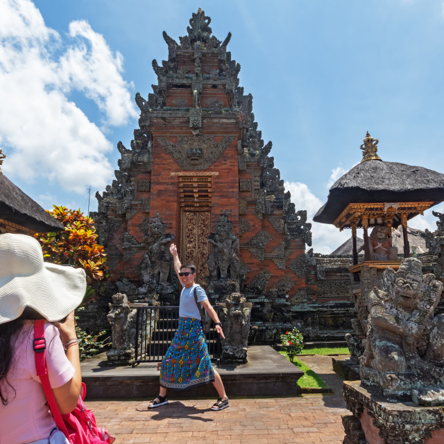 """Bali, Indonesia - September 15, 2018: Tourist taking photo at Puseh temple, located at Batuan village. It is a Balinese temple with interesting stone carvings & sculptures."" stock image"