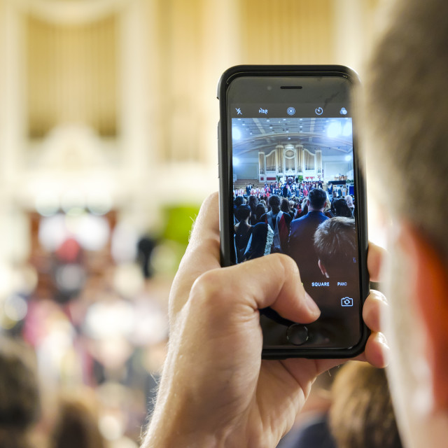 """Hand holding smartphone photographing event"" stock image"