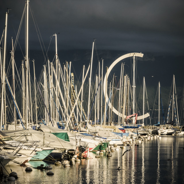 """Yachts under dark clouds at the port of Ouchy, Lausanne"" stock image"