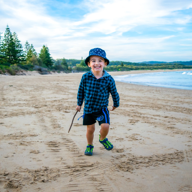 """Happy boy running on beach"" stock image"