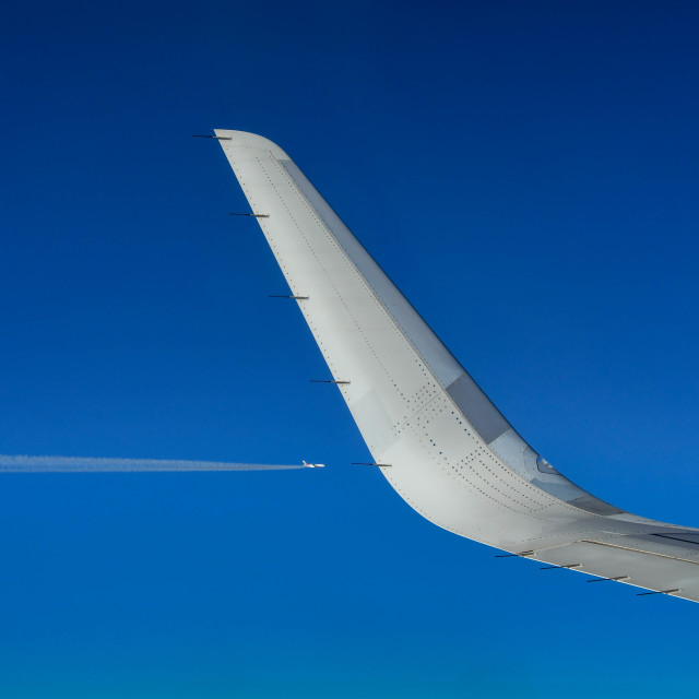 """""""Wing tip of a passenger jet against a deep blue sky"""" stock image"""