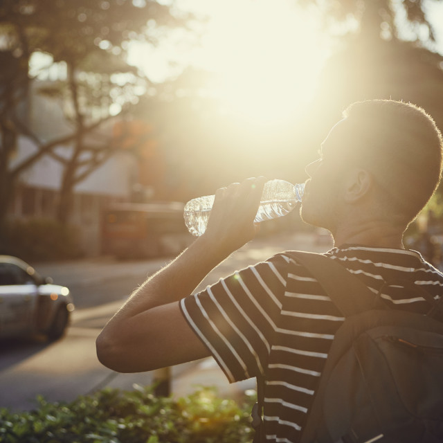 """Man drinking water at sunset"" stock image"